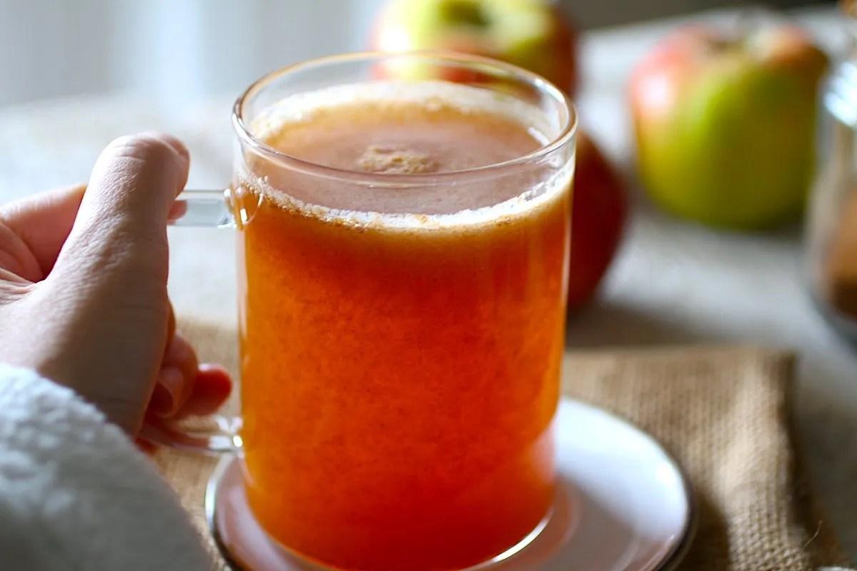 Una mano che tiene la tazza trasparente con il succo di mele su un piattino