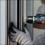 Montage Fingerschutz an Metall-Tür im Eingang
