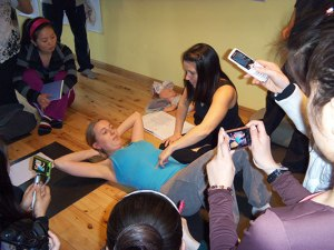 Jennifer checking a postnatal student for Diastisis Recti; the separation of the abdominal muscles after pregnancy.