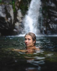 woman swimming in bish bash waterfalls looking back