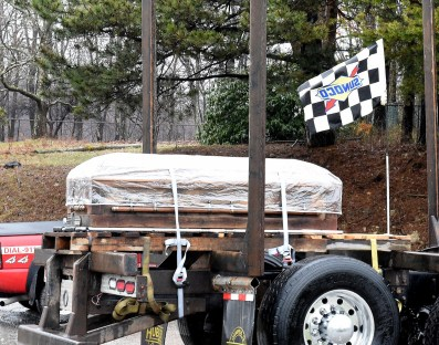 Okey Dalton rest on log truck driven by his son Darrin Dalton checker flag flies as Okey was racing fan.