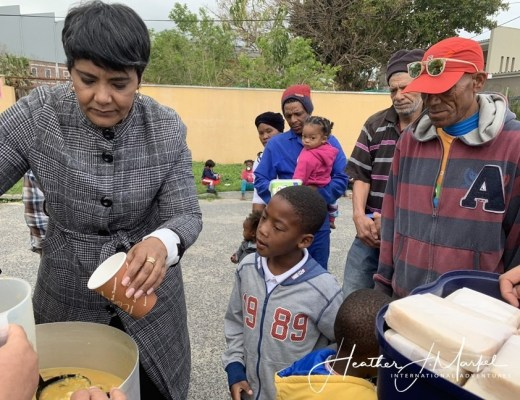 woman serving soup to african families in squatter camp polyoak south africa