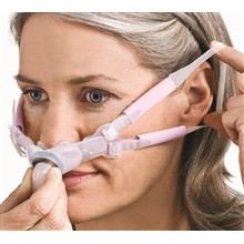 "Woman receiving non-invasive ventilation thru plastic tubes in nose. These are called ""nasal pillows."""