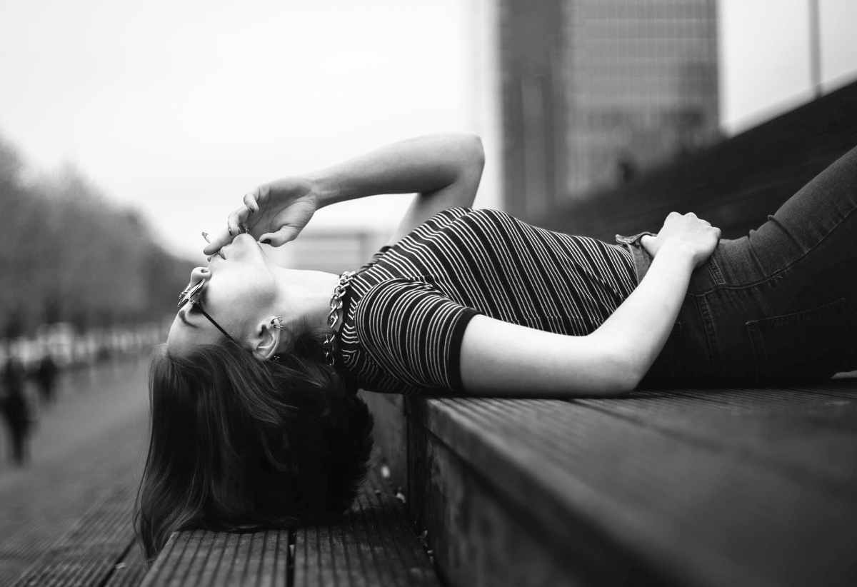 woman laying on stairway grayscale photo