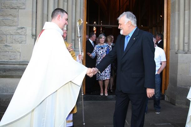 Neighbour John Baird congratulates Fr Gorman following his ordination Photo Brian McDaid