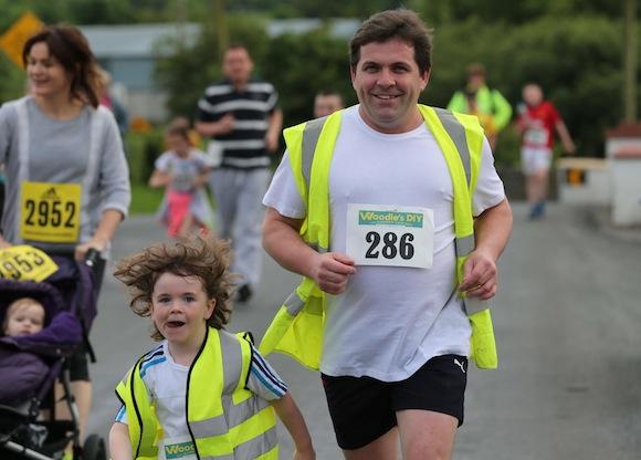 Former Sean Mac Cumhaills' player Martin Mc Laughlin shows the next generation how it is done during the Sessiaghoneill NS 5K Fun Run & Walk. Pic.: Gary Foy, newsandsportfiles
