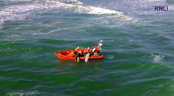 Dramatic rescue: The surfers being brought onto the lifeboat this evening