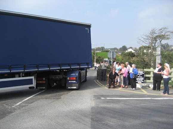 A lorry tries to navigate around Cockhill Bridge in Buncrana as protestors look on.