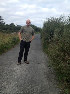 The Independent county councillor stands at some overgrown hedges.