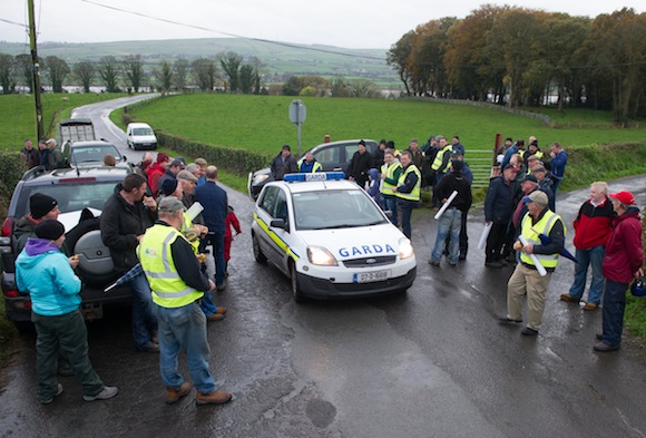 Garda checking out the protest by members of Donegal IFA as they blockade the Donegal / Foyle Meat's Factory Carrigans as part of there nationwide protest at the low prices being paid for cattle. Photo- Clive Wasson
