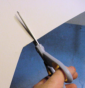 Cutting-paper-board-with-scissors