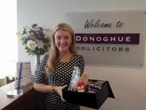 Photo of Hannah Bickley with a gift box from a grateful client following settlement of his accident claim.