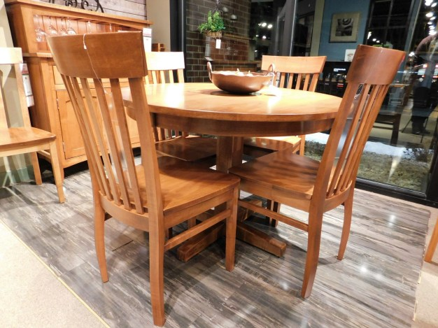 """Round Madison Single Pedestal Table with 2 12"""" Leaves & Eased Edge Wood Species Shown: Brown Maple Dimensions: 42""""W x 66""""L (open) Fully Customizable. Shown with Venice Chairs. Please contact us for pricing details."""