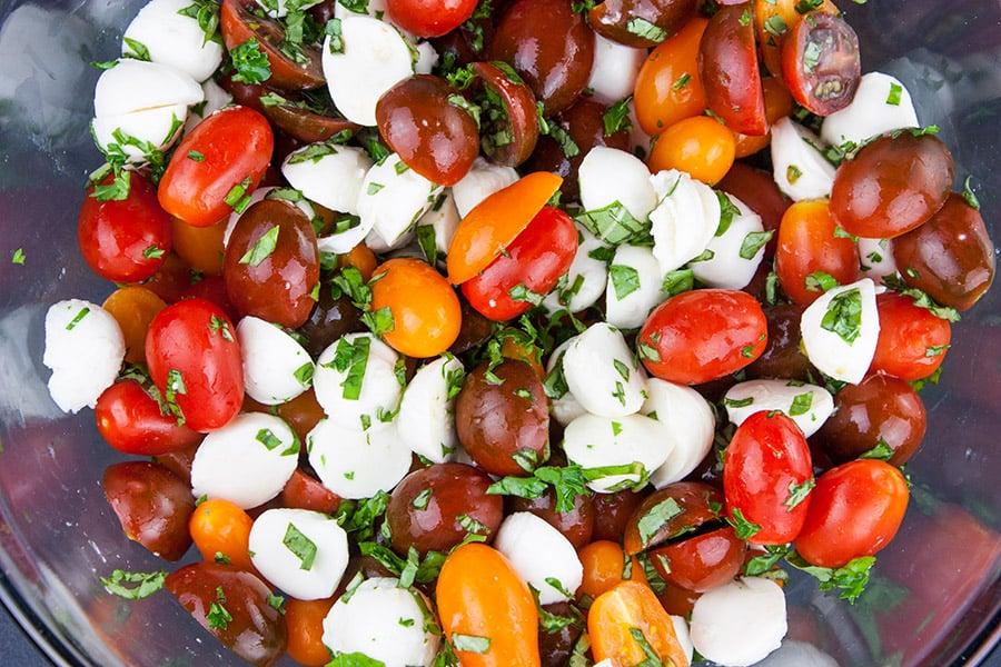 Kumato tomatoes, Ciliegine mozzarella and fresh basil in a glass bowl