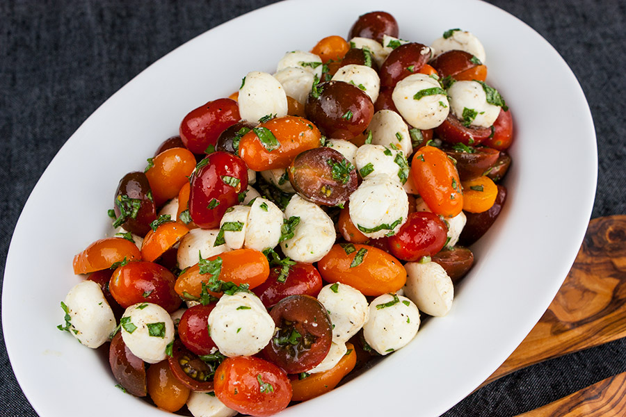 Fresh Tomato Mozzarella Salad in a white oval bowl with wooden spoons