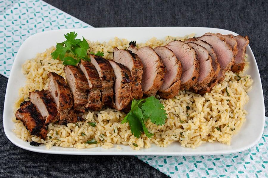 Grilled Adobo Pork Tenderloin - Sliced pork tenderloin on a bed of cilantro lime rice