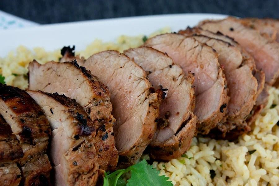 Grilled Adobo Pork Tenderloin - Closeup of pork tenderloin on a bed of cilantro lime rice
