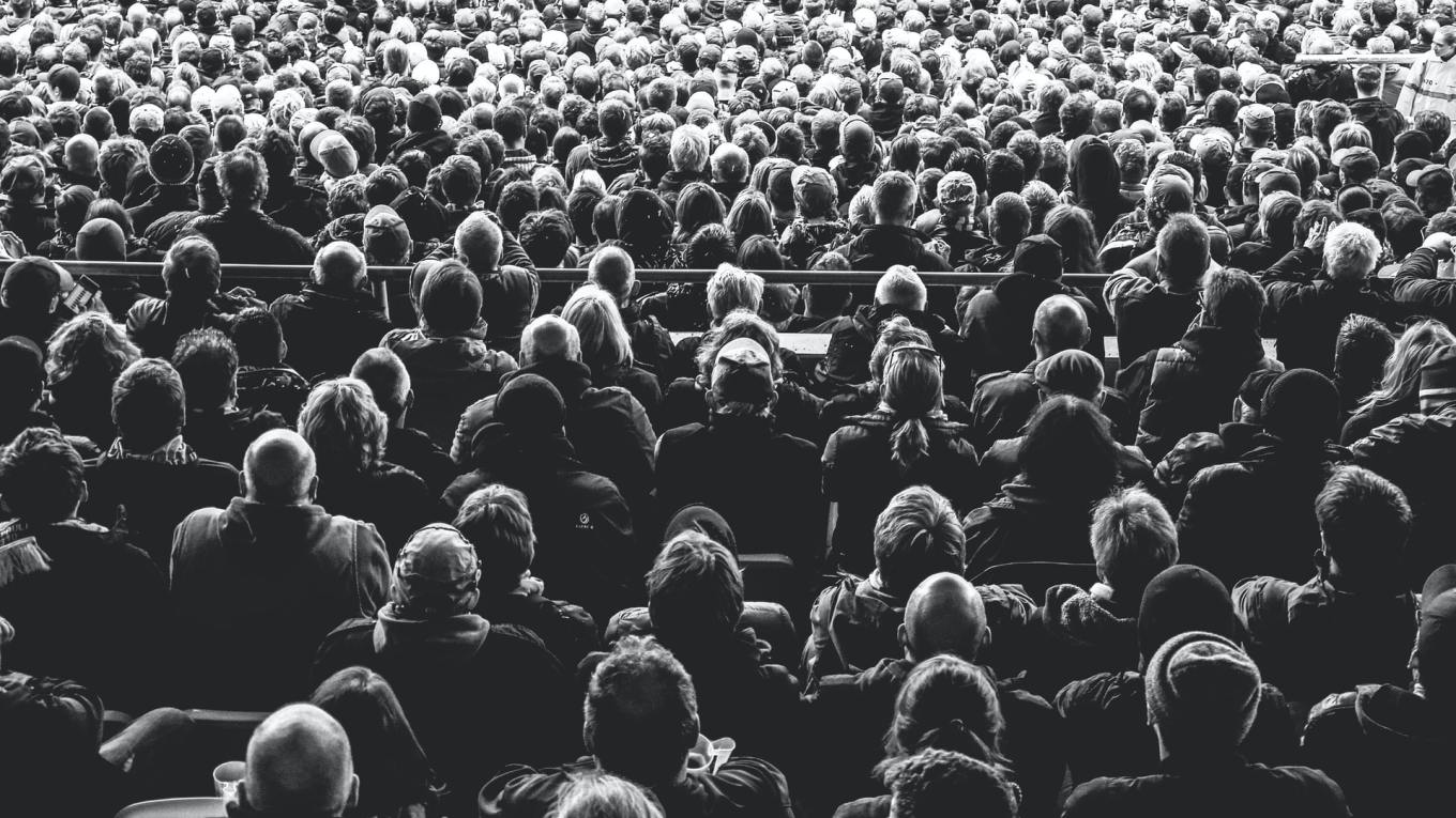 Black and white photo of crowd looking away from the camera towards a stage