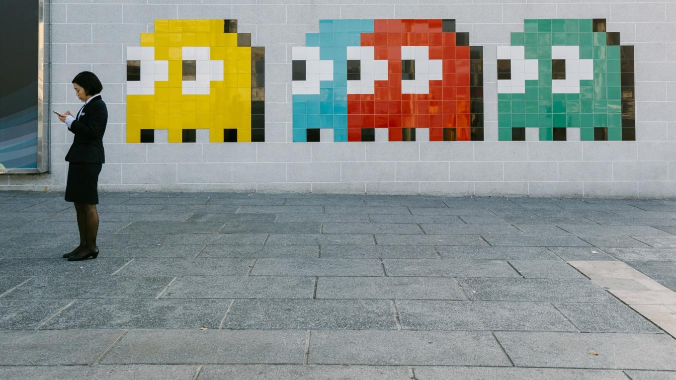 Pac man characters painted on a wall, looking like they're following a person walking past