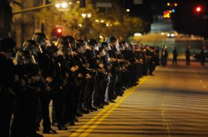 LOS ANGELES, CA - NOVEMBER 28:  Hundreds of Los Angeles Police Officers in riot gear form a skirmish line as they attempt to clear the streets around Los Angeles City Hall of Occupy LA demonstrators after the deadline to dismantle the occupy campsite expired on November 28, 2011 in Los Angeles, California. Los Angeles Mayor Antonio Villaraigosa last week gave the protesters outside City Hall until 12:01 am today to dismantle their protest campsite and leave.  (Photo by Kevork Djansezian/Getty Images)