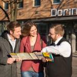 Dorint-Mitarbeiter zeigt Pärchen den Weg auf dem Stadtplan