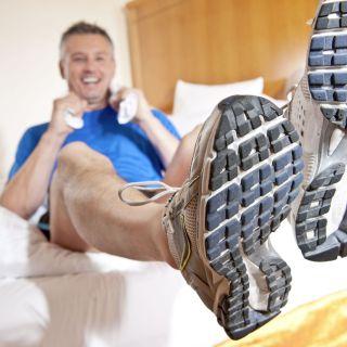 Läufer nach dem Ahrathon sitzend auf seinem Bett