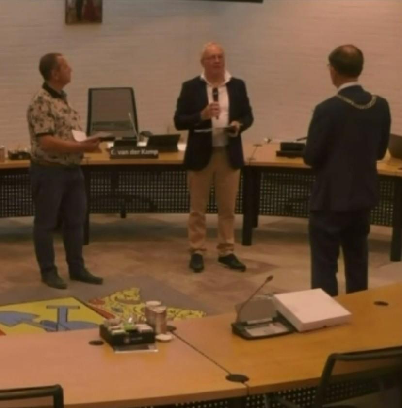 leden van de WIN bieden het ansichtkaartenboekje aan aan burgemeester Van der Kamp