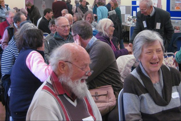 A number of people in a hall, chatting and smiling