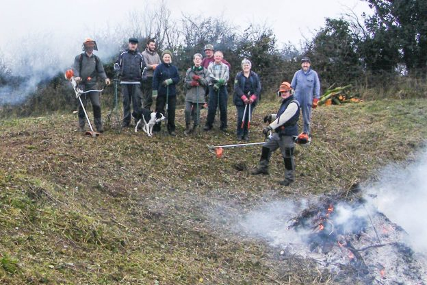 A group of people in a field, with the dip of a pit in front of them; two are holding cutting equipment and there is a bonfire