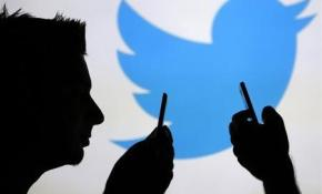 Men are silhouetted against a video screen with an Twitter logo as he poses with an Samsung S4 smartphone in this photo illustration taken in the central Bosnian town of Zenica, August 14, 2013. REUTERS/Dado Ruvic