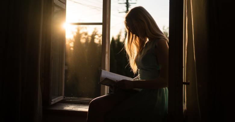 Branje knjige ob sončnem zahodu