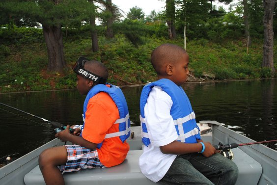two boys fishing and boating back to back