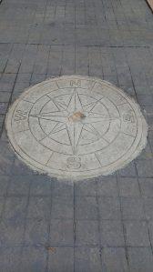 concrete compass embedded in cobblestone sidewalk