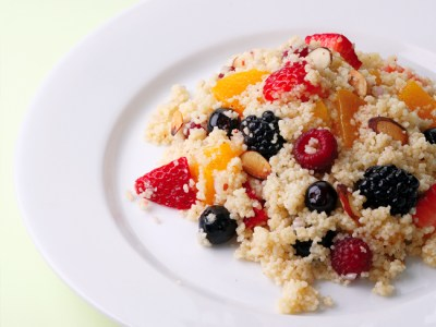 Couscous and fruit salad on a white plate