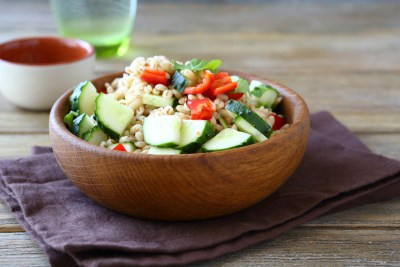 Pearl barley with cucumbers and pepper in a wooden bowl. Salad, healthy food