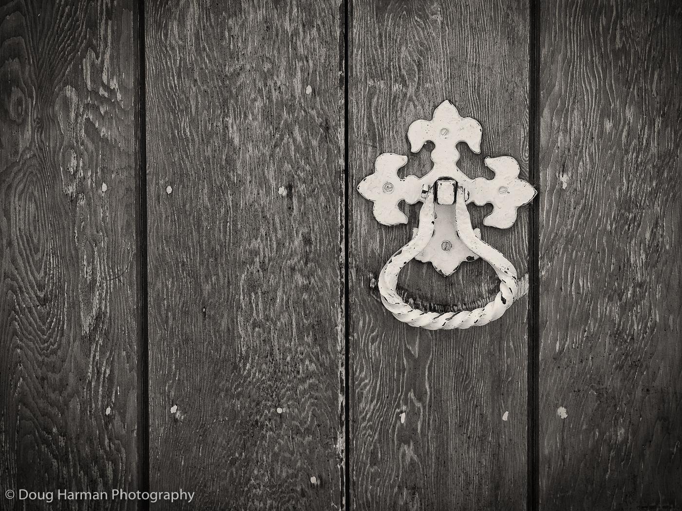 A door knocker on a wooden door. Enhanced in NIK's Silver Efex Pro.