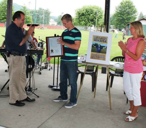 Pastor Joseph re-presented proclamation to Zach at the anniversary celebration at the park.