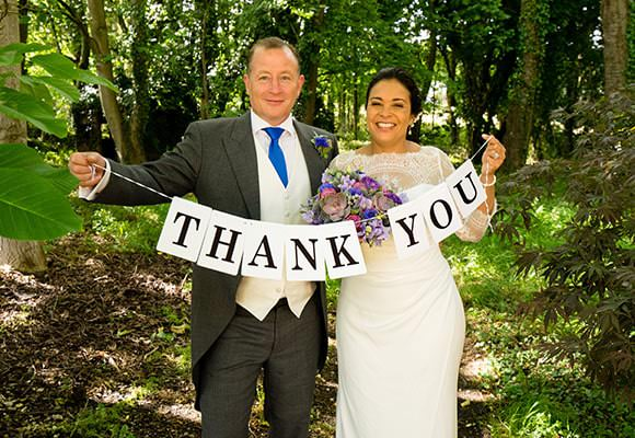 Wedding Photograph - couple with thank you sign for cards