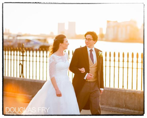 Wedding couple walking next to the river in Greenwich. Caught in the evening light.