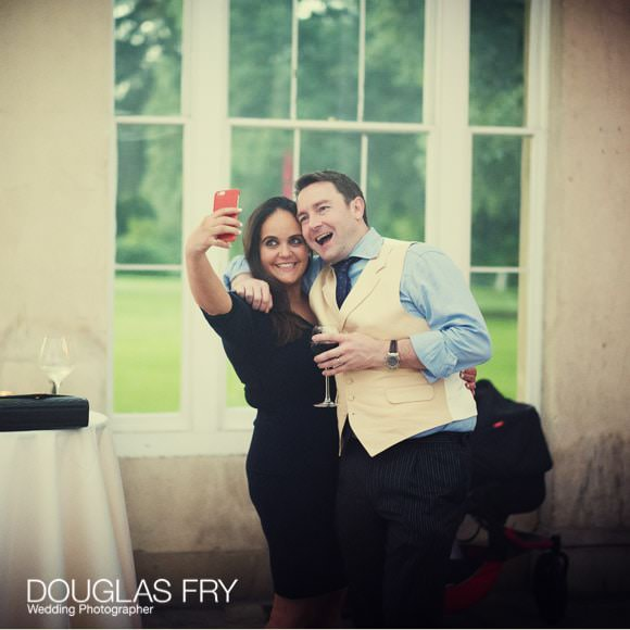 Guests taking selfie at Syon park in the Great Conservatory during wedding reception