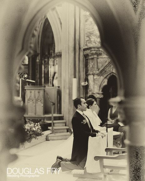 Photograph of bride and groom in Farm Street Church, Mayfair at alter in black and white