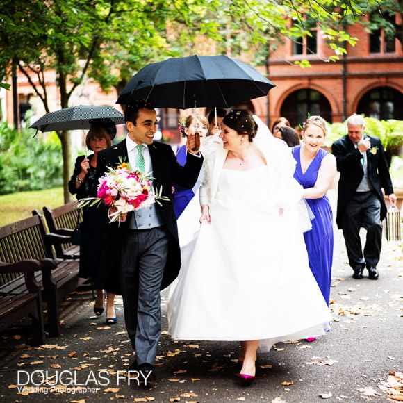 Bride and Groom walking with umbrella in London