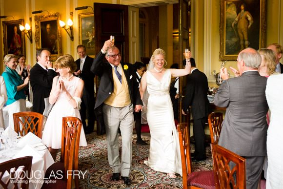 Bride and Groom entering wedding breakfast with raised champagne glasses