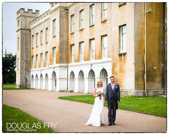 Bride and groom walking with Syon House behind