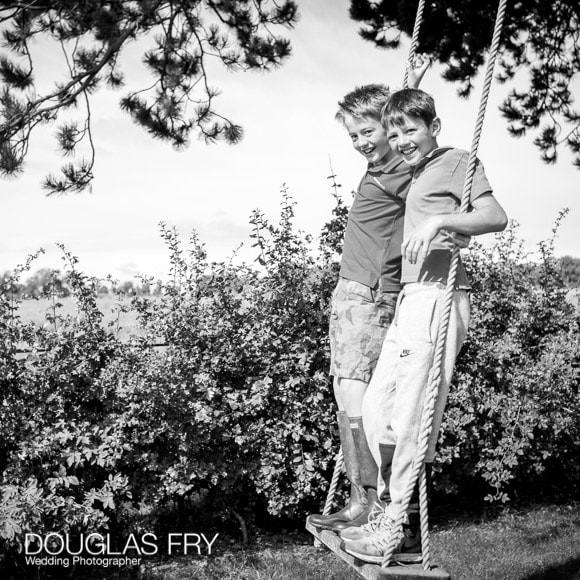 Boys standing on swing in garden - black and white photograpgh