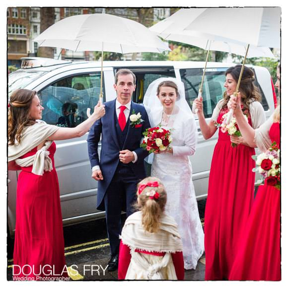 Bride and father arriving at Soho church in London with umbrellas