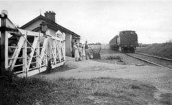 The Marshallstown Road level crossing on the Ardglass line, just outside Downpatrick in 1949 - with the Curran family operating the ground frame to let No. 27 pass.