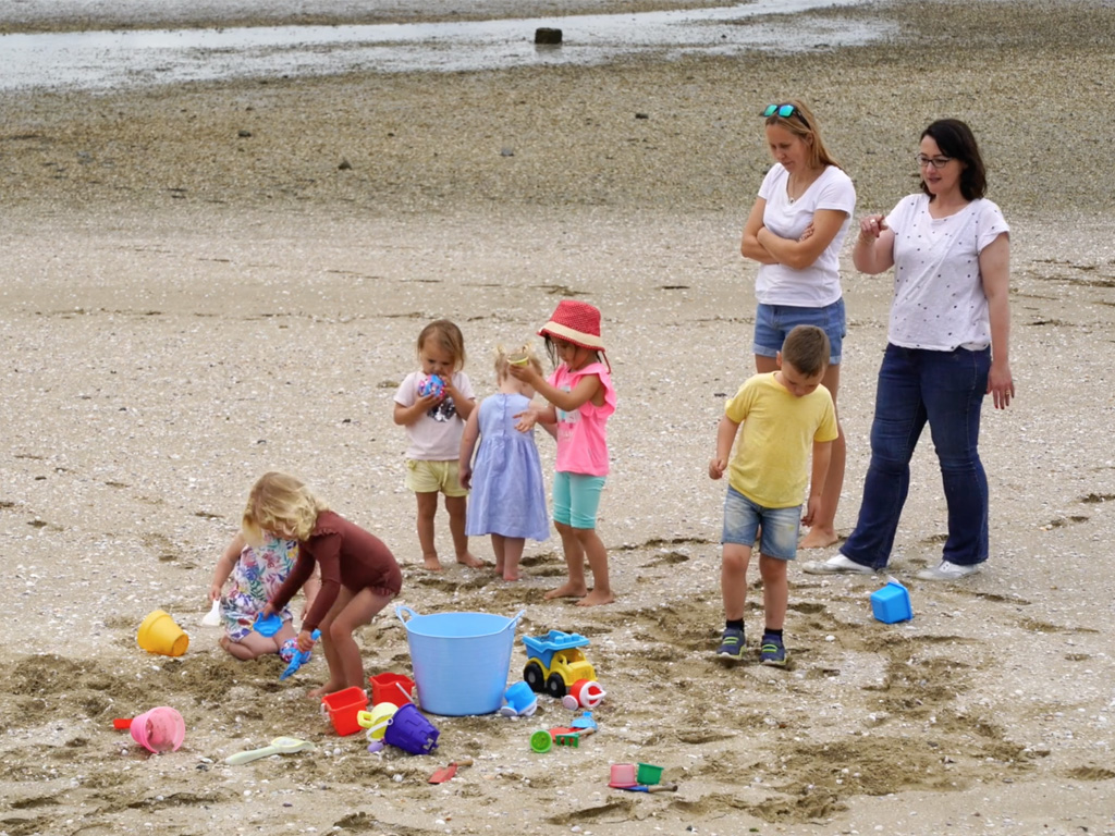 Group of young kids on the beach with adult supervision