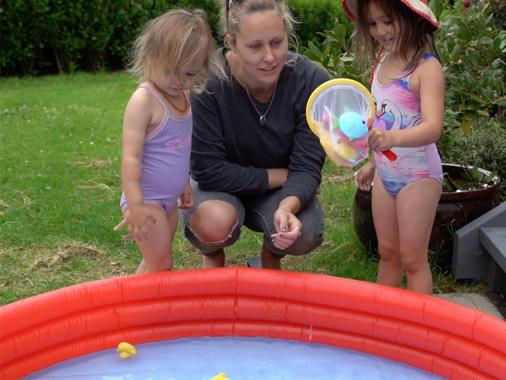 Mum supervising kids by paddling pool