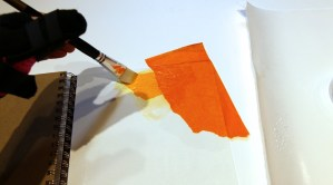 Gluing down an overlapping piece of tissue paper.